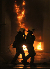 Riot police walk past a building burning during violent protests in central Athens