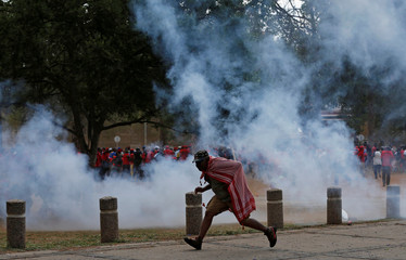 A protestor runs for cover as police officers fire stun grenades during a march to call for the removal of President Jacob Zuma outside the Union Buildings in Pretoria