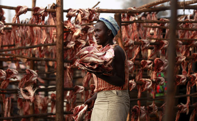 "A fish trader carries dried fish skeletons outside her stall at the Obunga ""mgongo-wazi"" fish frying market in Kisumu"