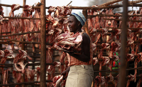 """A fish trader carries dried fish skeletons outside her stall at the Obunga """"mgongo-wazi"""" fish frying market in Kisumu"""