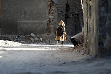 A child carries a school bag near damaged buildings in Harasta