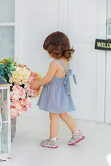 A little girl in a striped dress prepares to meet the groom, corrects a huge bouquet of flowers, playing house