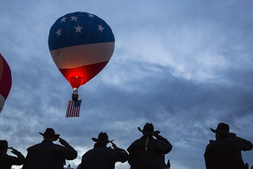 Police officers salute as the Star Spangled Banner is played to mark the beginning of a lift off during the 2015 Albuquerque International Balloon Fiesta in Albuquerque, New Mexico