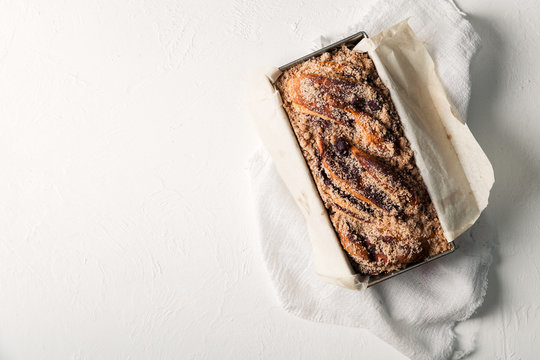 Chocolate babka in a baking tray with parchment sheet on white textured background. Homemade cocoa bun with baking utensils. Traditional french cuisine