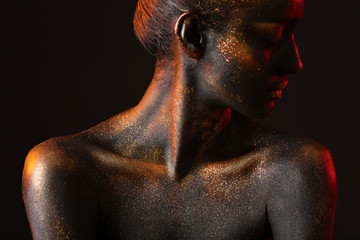 Portrait of beautiful young woman with dark paint and sparkles on her body, black background