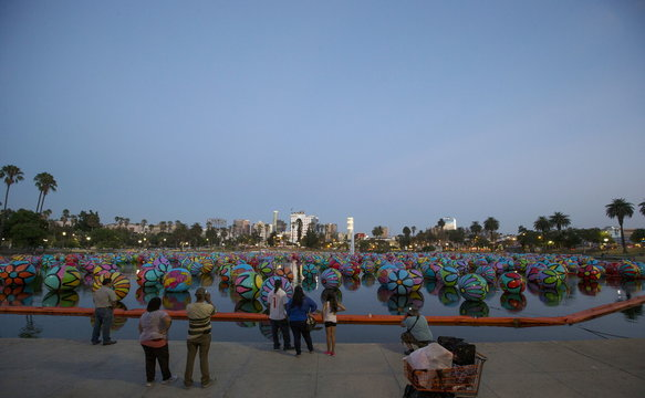 """People look at inflated spheres in MacArthur Park Lake, with the downtown skyline in the background, as part of Portraits of Hope's exhibition """"Spheres at MacArthur Park"""" in Los Angeles, California"""