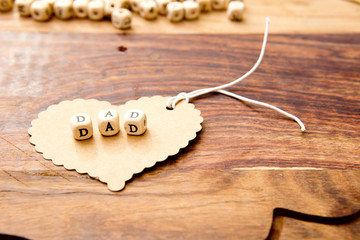Father's Day - Dad on cardboard heart on wood grain background