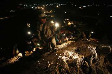 People look for precious stones in the mine dump piled by major mining companies at a jade mine in Pharkant