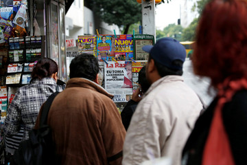 """People look at the front pages of local dailies with one headline reading """"The United States turns populist"""" at a newspaper stand in Mexico City"""