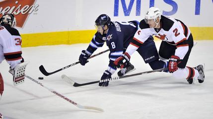 Winnipeg Jets' Burmistrov carries the puck around the net past New Jersey Devils' Foster during their NHL hockey game in Winnipeg