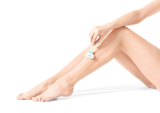Beautiful young woman shaving legs on white background