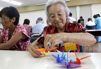 Toyoko Suzuki makes origami cranes to support Japan's earthquake and tsunami victims in Lima