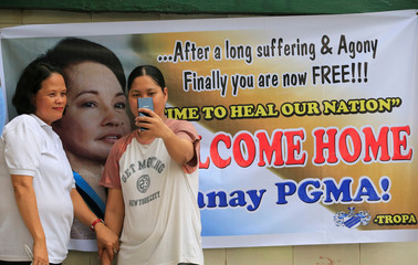 Supporters of former Philippine President Gloria Macapagal Arroyo takes a selfie picture in front of a banner of Arroyo before her release from hospital arrest at the Veterans Memorial Medical Center (VMMC) in Quezon city