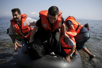 Syrian refugees prepare to jump off a dinghy as they arrive on the island of Lesbos