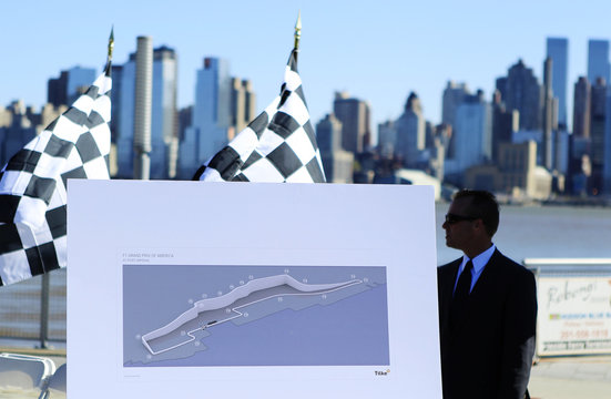 A public relation staff stands behind a race course map before an announcement that New Jersey will host Formula One world championship series in Weehawken