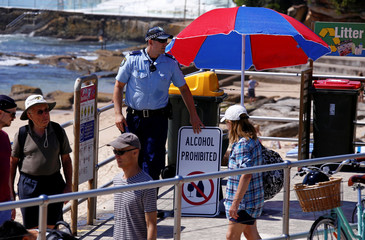 A policeman adjusts a sign declaring that no alcohol is allowed to be brought onto Sydney's Bondi Beach on Christmas Day in Australia