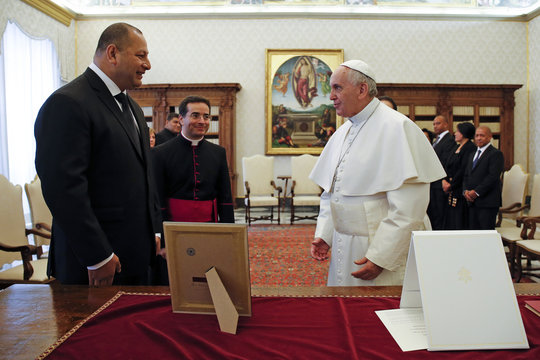 Pope Francis exchanges gifts with Tonga's King Tupou VI during a private audience at the Vatican
