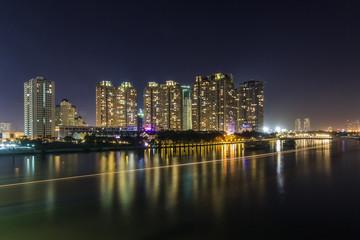 SAIGON, VIETNAM - DEC 27, 2016 - Night on the Saigon River, across the river is Saigon Pearl luxury apartment and a big construction site