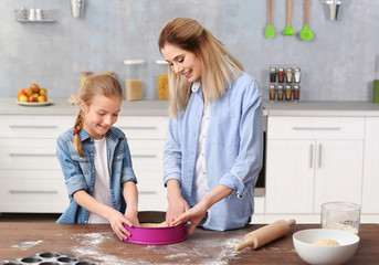 Young woman and her daughter cooking in kitchen