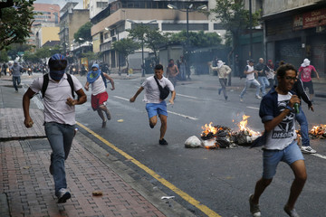 Opposition students run from police and past burning trash as they protest against President Nicolas Maduro's government in Caracas