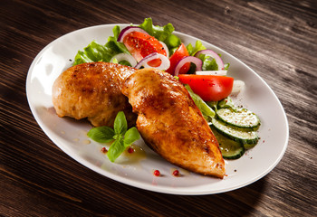 Grilled chicken fillet on wooden table