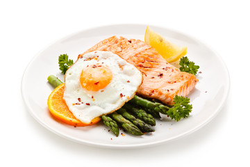 Griilled salmon with asparagus and fried egg on white background