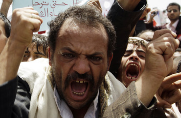 Anti-government protesters shout slogans during a rally to demand the ouster of Yemen's President Ali Abdullah Saleh outside Sanaa University