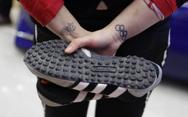 """Britain's two-women bobsleigh pilot Paula Walker holds her protective shoes as she waits for the start during a practice session at the """"Sanki"""" sliding center near Krasnaya Polyana, a venue for the Sochi 2014 Winter Olympics near Sochi"""