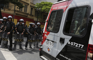 Members of Brazil's Movimento dos Sem-Teto look out from a police van after being detained in Sao Paulo