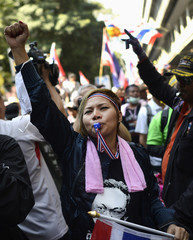 Anti-government protesters shout as they break down the barriers at the Thai Police Headquarters in Bangkok