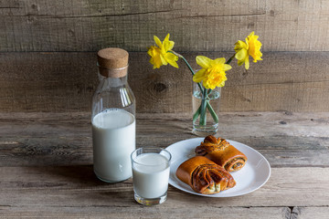 Glass and bottleof milk , biscuit and flowers on wood background