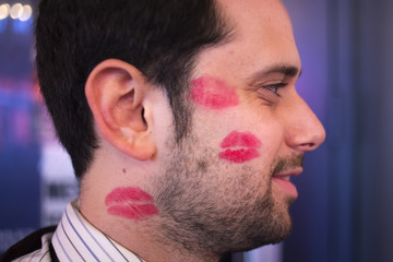 A man is seen with lipstick kisses on his cheek as he takes part in Halloween festivities in Times Square