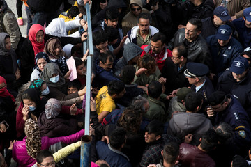 Refugees and migrants, most of them Afghans, block the entrance of the refugee camp at the disused Hellenikon airport as police officers try to disperse them, in Athens