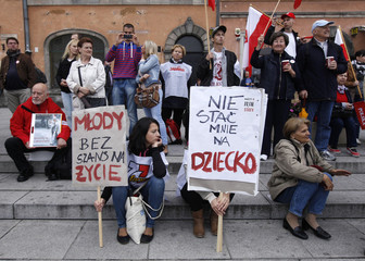 Protesters hold signs during an anti-government protest in Warsaw