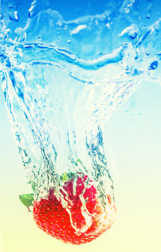 strawberry falling in water, leaving splashes and bubbles