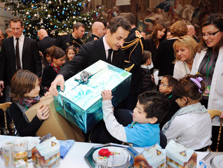 France's President Sarkozy gives a present to a child during the Christmas party at the Elysee Palace in Paris