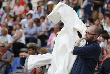 Priest puts on a robe before the arrival of Pope Francis during a meeting of Renewal of the Holy Spririt organization in Rome