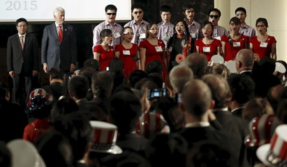 Bill Clinton and Pham Binh Minh listen as a choir performs the Vietnamese anthem during an event celebrating the 239th anniversary of the U.S. Independence Day in Hanoi