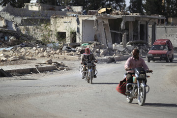 Men ride motorcycles past damaged buildings in al-Rai town, northern Aleppo countryside