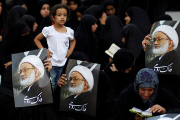 Supporters hold posters of Bahrain's leading Shi'ite cleric Isa Qassim during a sit-in outside his home in the village of Diraz west of Manama