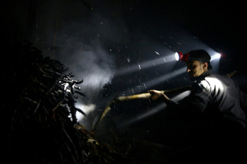Civil defence members try to put out a fire at a site hit by an airstrike in the rebel held besieged Douma neighbourhood of Damascus