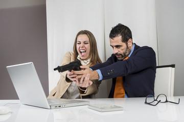 Manager con pistola  con accanto la sua segretaria spara verso il computer in segno di vendetta