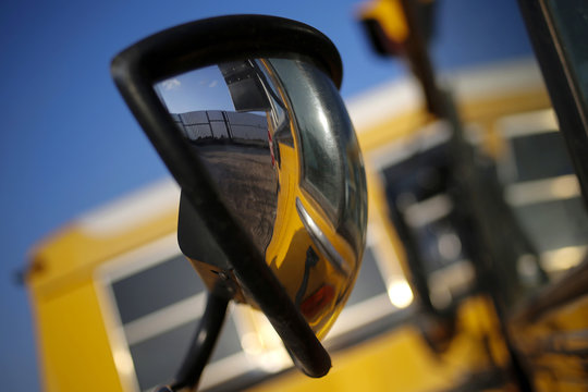 The border fence at the United States-Mexico border is seen reflected in a school bus mirror outside Brownsville