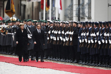 German Chancellor Merkel and France's President Sarkozy inspect honour guard during a welcome ceremony at the Muensterplatz in Freiburg