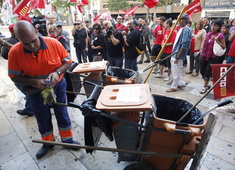 Picketers march past a municipality worker in central Valencia during a nationwide general strike