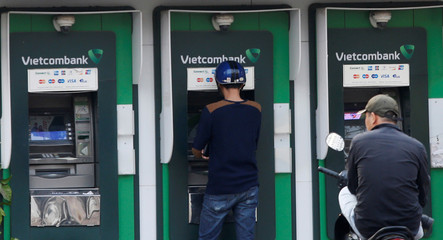 A man withdraws money from an ATM at a branch of Vietcombank in Hanoi