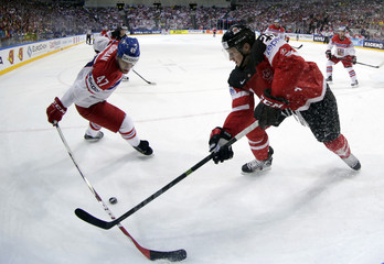 Jordan of the Czech Republic fights for the puck with Canada's MacKinnon during their Ice Hockey World Championship semifinal game at the O2 arena in Prague