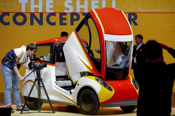 People take pictures of a high-efficiency petrol-burning concept car as it is unveiled by Royal Dutch Shell during a ceremony in Beijing