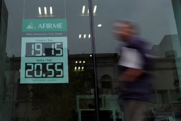 Man walks past a board displaying the exchange rate of Mexican peso against the U.S. dollar at an Afirme bank branch in Monterrey