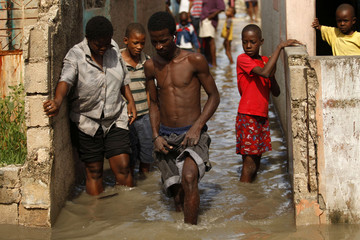 Haitians walk in a street after a drain flooded their neighborhood of Cite-Soleil in Port-au-Prince